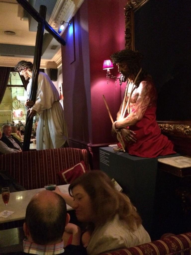 """Bar """"Puerta Oscura"""" in Málaga, unweit der Kathedrale: Ein Ort, an dem sich Wege kreuzen, die unterschiedlicher kaum sein können. Ob sich manchem Gast angesichts der Ausstellung zur Semana Santa am Cocktail verschluckt hat?"""